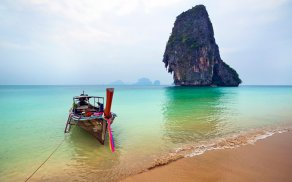 Fishing boat tied on a beach near limestone cliff, Railay Beach